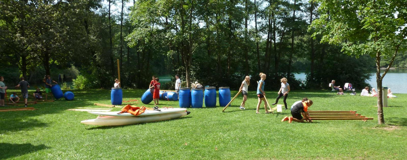 Kinder und Jugendliche beim Floßbauen während des Sommerferienprogramms