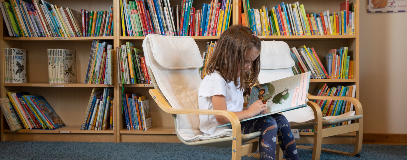 Kind liest ein Buch in einer Leseecke