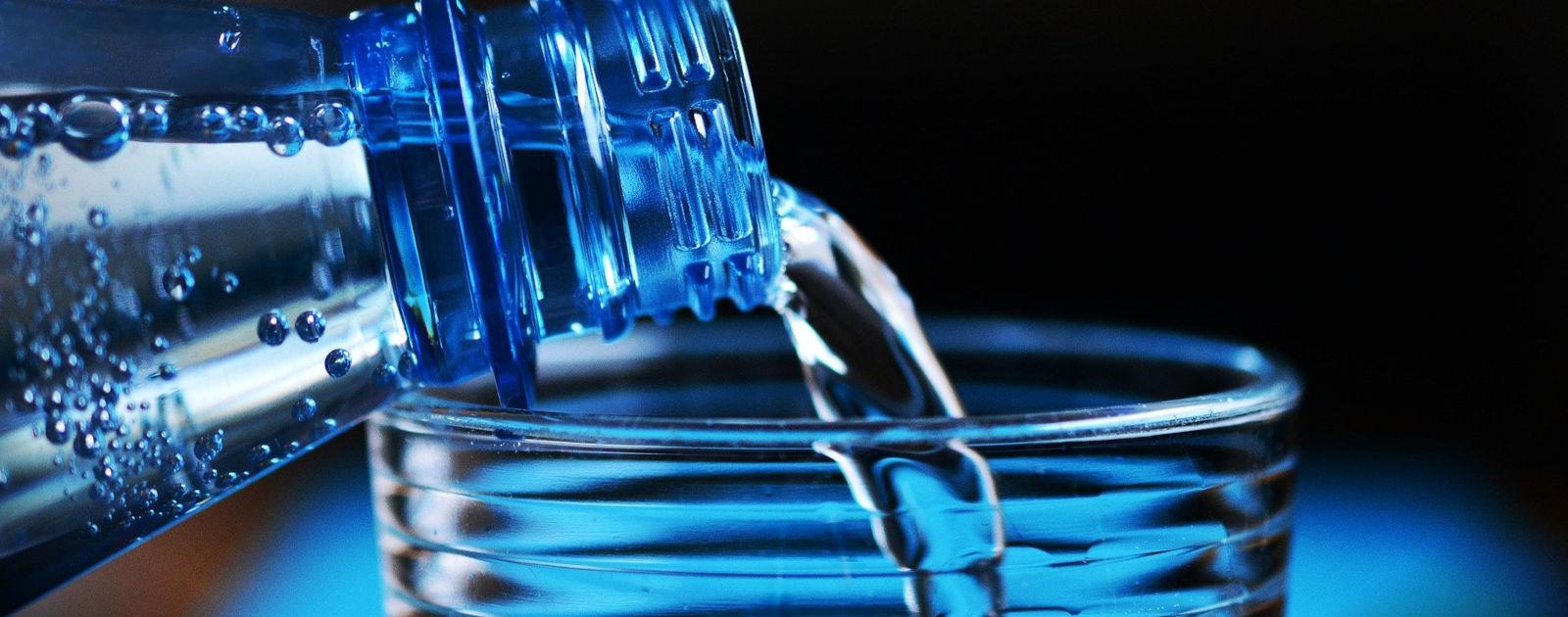 Wasser aus einer Flasche wird in ein Glas eingeschenkt