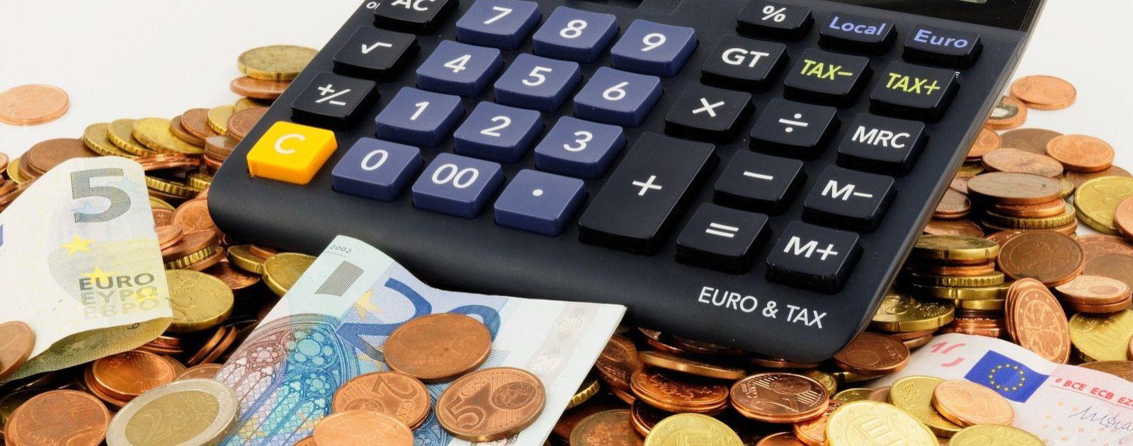 Euro Münzen und Scheine darauf liegend ein Taschenrechner