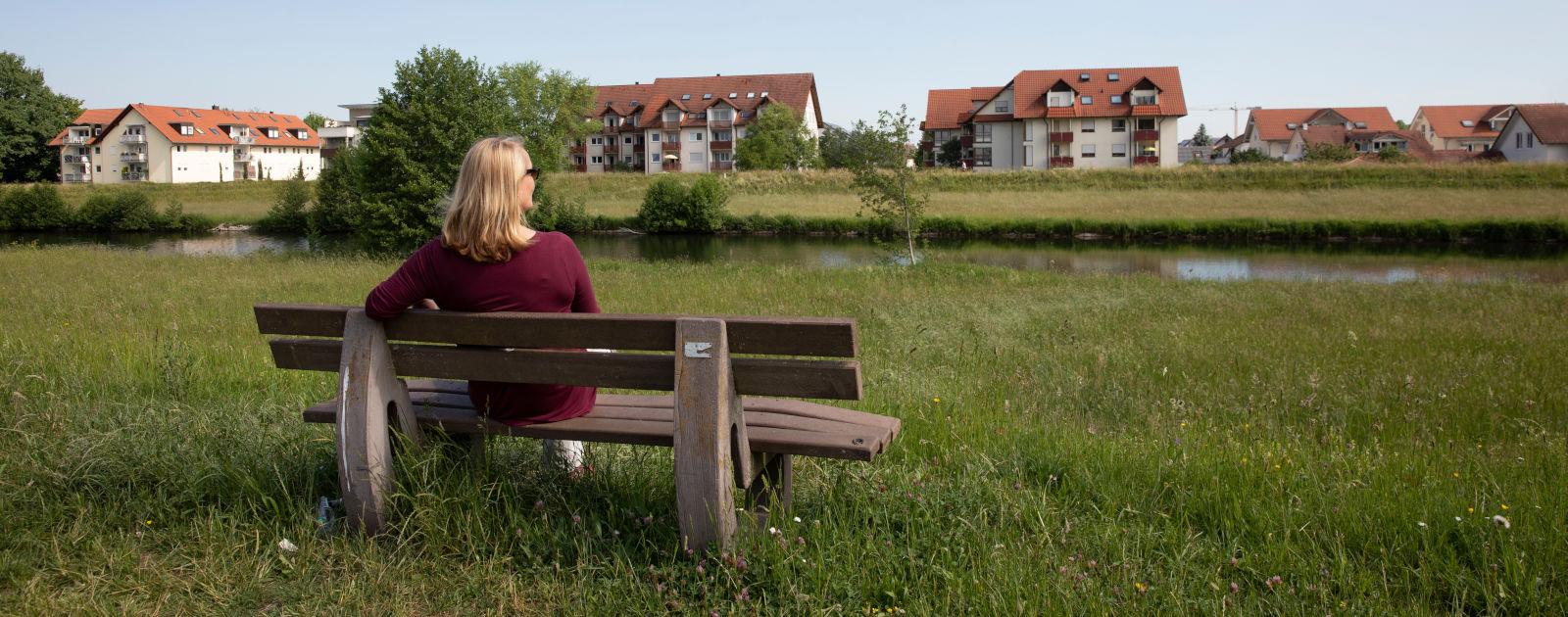 Frau sitzt auf einer Bank an der Kinzig in Willstätt