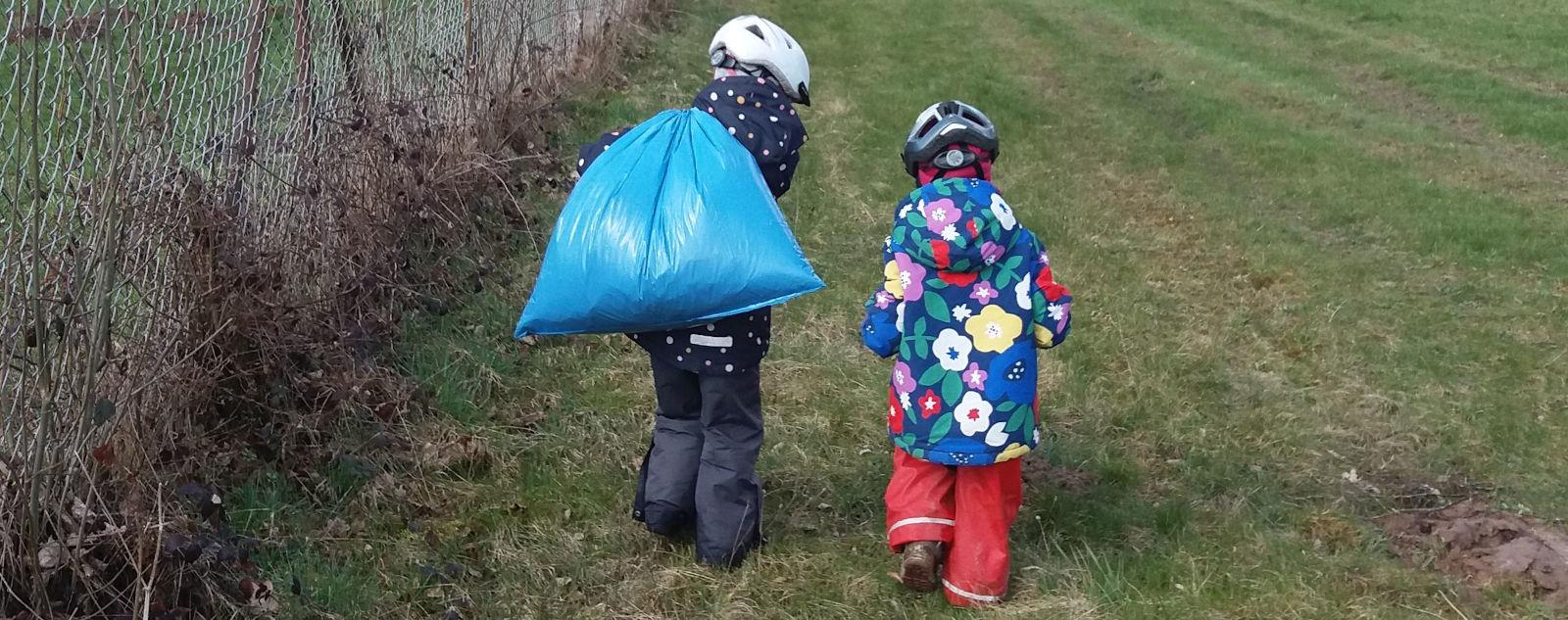 Zwei Kinder auf einer Wiese. Eines der Kinder trägt einen vollen Müllbeutel über die Schulter - Frühlingsputzaktion
