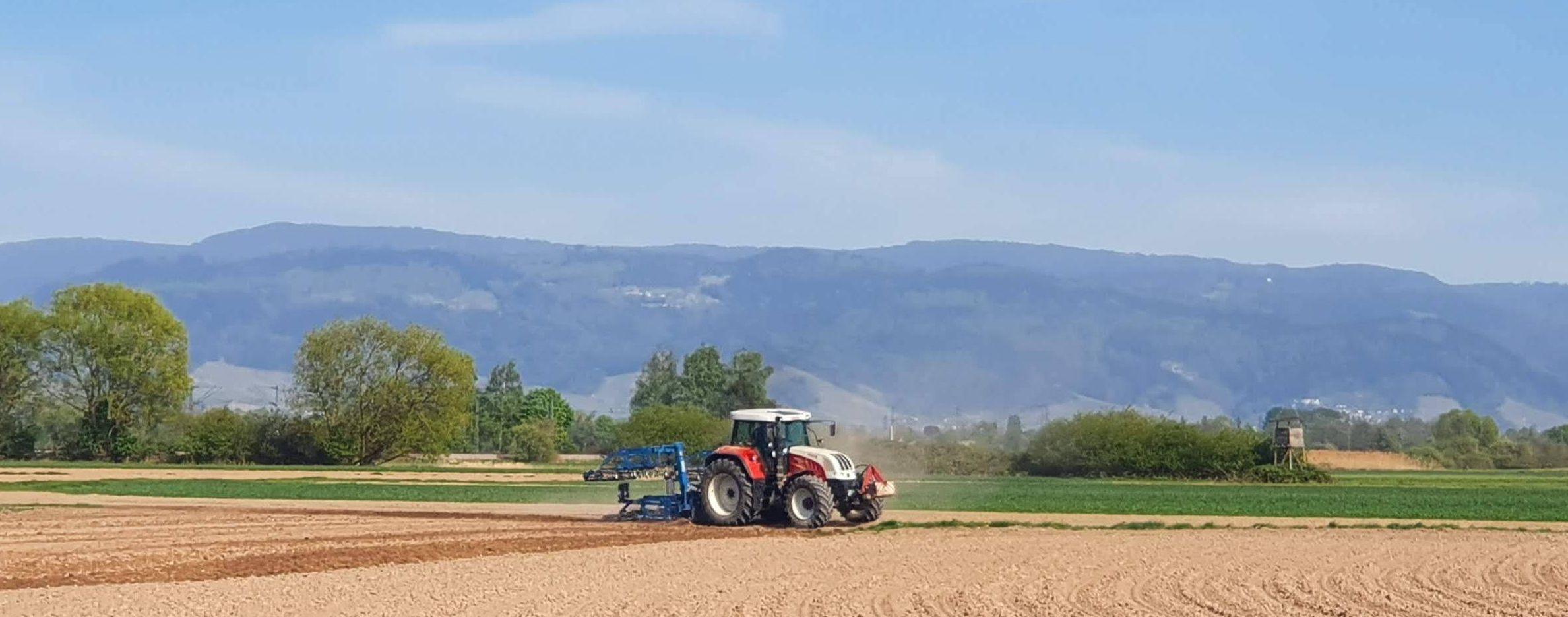 Traktor auf Acker bei Hesselhurst mit Schwarzwald im Hintergrund